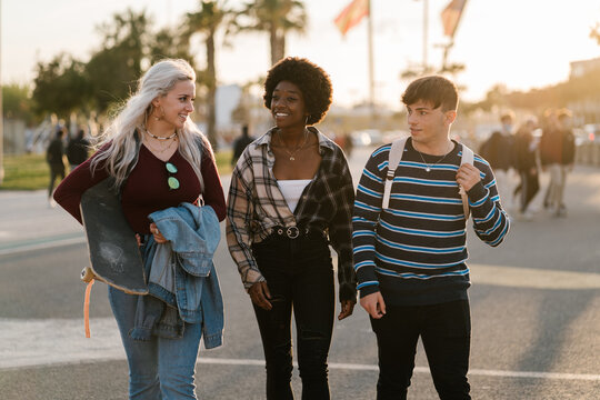 Diverse friends walking and talking on street