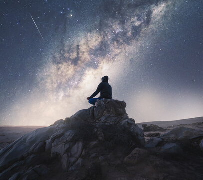 person meditating at night under the Milky Way