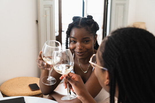 Relaxed black ladies clinking with wineglasses at home