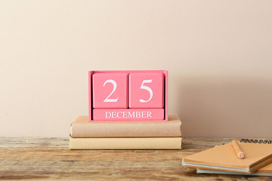 Cube calendar with date DECEMBER 25 and books on table in room