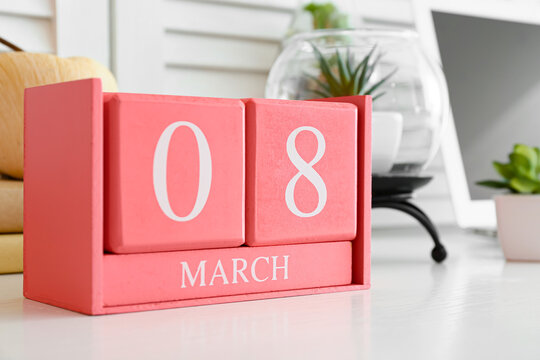 Cube calendar with date MARCH 8 and houseplant on table in room, closeup