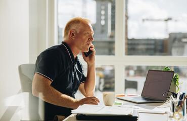 Fototapeta Senior businessman talking on phone obraz