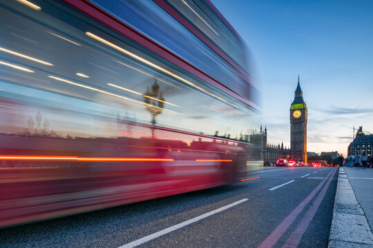 Red double-decker bus on Westminster Bridge at night, London, Great Britain
