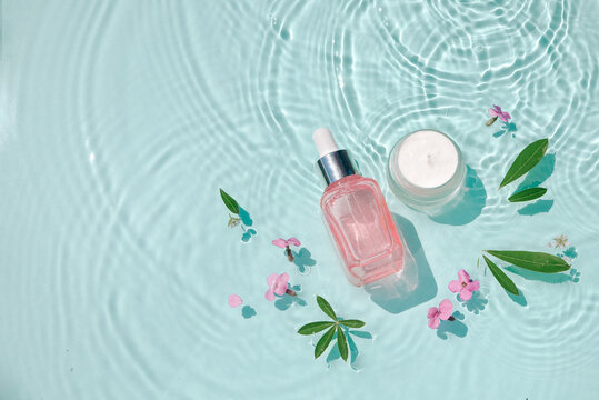 Moisturizing cosmetic products on water with drops. Serum glass bottle and cream jar on aqua surface Concept moisturizing summer beauty treatments