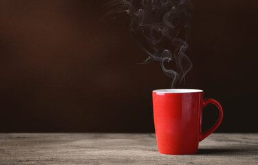 Red cup of hot coffee with coffee smoke on wood.