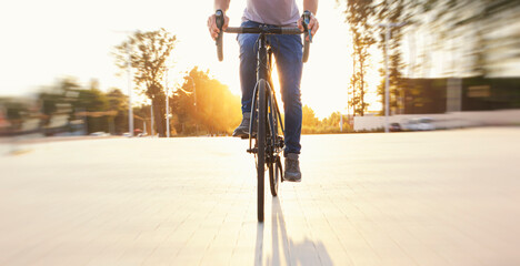 The cyclist in casual clothing riding the bicycle in the evening
