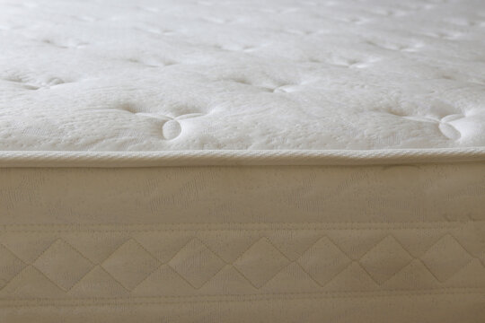 Close up shot of white orthopedic mattress surface pattern with a lot of copy space for text. Hypoallergenic foam matress for proper spinal alingment and pressure point relief. Background, top view.