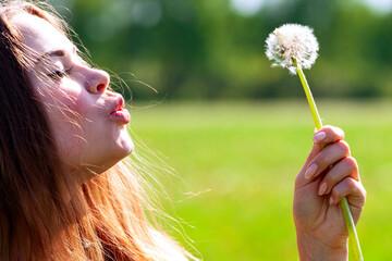 Obraz Woman blowing on a dandelion - fototapety do salonu
