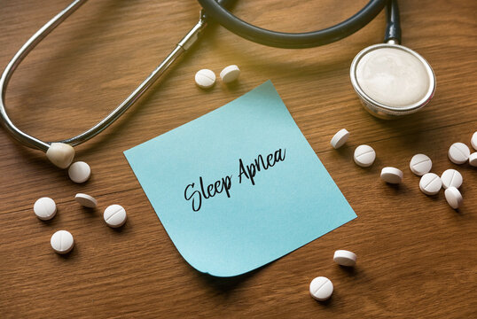 Selective focus of stethoscope, white medical pills and blue memo note written with Sleep Apnea on wooden background.
