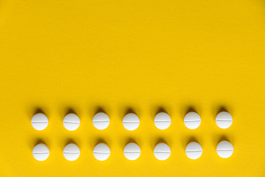 A row of white medical pills on yellow background with copy space.