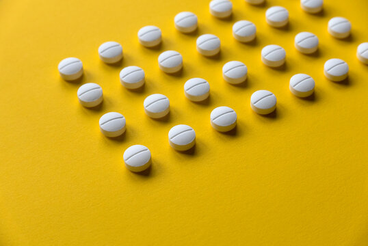 A row of white medical pills on yellow background.