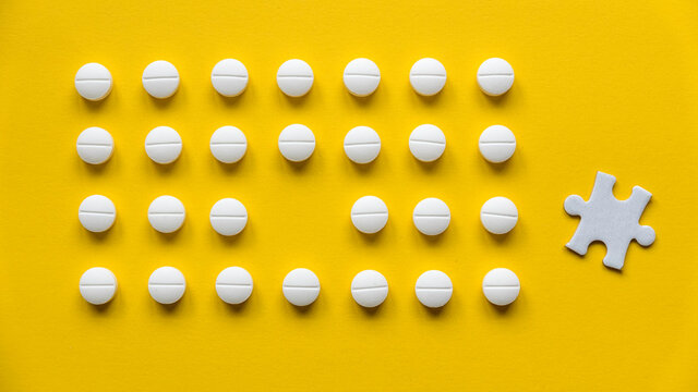 A row of white medical pills on yellow background with one missing spot in the middle and a piece of jigsaw puzzle.