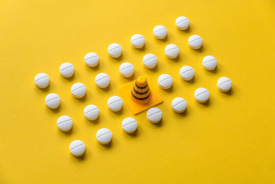 A row of white medical pills on yellow background with one missing spot in the middle fill by safety cone.