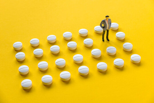 A row of white medical pills on yellow background with one missing spot in the middle fill by a men.