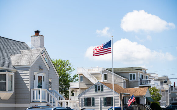 American flag waving in the wind in front of beach houses celebrating the 4th of July, Long Beach Island, NJ, LBI background.