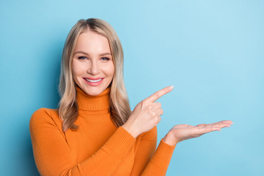 Photo of sweet pretty young woman dressed orange pullover smiling holding arm pointing empty space isolated blue color background