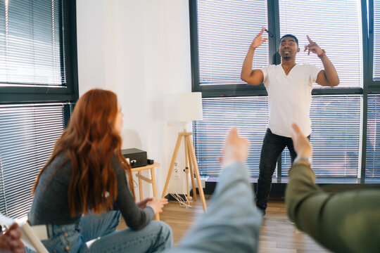 Back view of cheerful African American male playing charades with friends showing pantomime by window in light office room. Diverse multi-ethnic colleagues playing in active games during team building