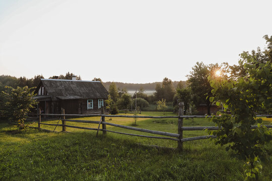 wooden european house in a picturesque countryside at sunset in summer