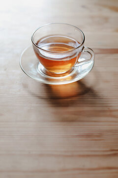 a glass cup of tea on a wooden table