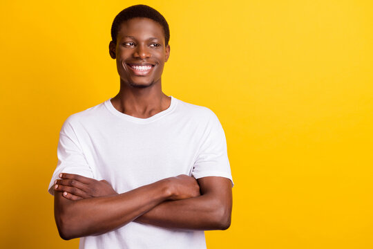 Photo of cool brunet young guy crossed arms look empty space wear white t-shirt isolated on yellow color background