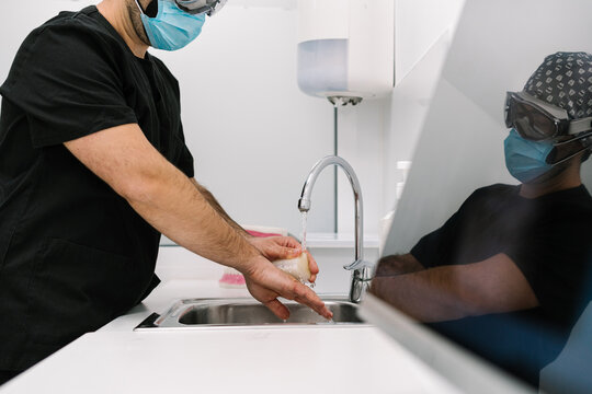 Doctor washing his hands in the hospital sink.