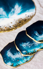 Cup holder, epoxy resin tray, marine-style stone cut. Blue stains of paint, gold trim. Subject for table setting. Gloss, reflection. The effect of the sea.