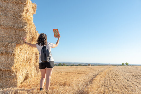 middle-aged brunette latina woman standing consulting a tablet leaning against a pile of straw bales