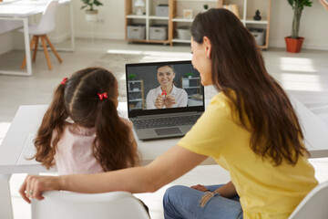 Fototapeta Back view happy school child together with mom sitting at desk table, looking at laptop, learning letters in online class, watching teacher's educational kids video in covid19 corona virus quarantine obraz