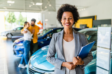 Obraz African American saleswoman working at car showroom. Customers in the background. - fototapety do salonu