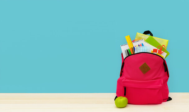 Back to school. Backpack for school or college with bright colorful school supplies on blue background. Stationery for school children's studies. Greeting card or banner for sale. Copyspace.