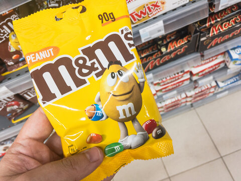 BELGRADE, SERBIA - JULY 4, 2021: M&M's logo on a pack of peanut flavored dragees. M&Ms is a brand of Mars company producing candy shell chocolates, multicolor, with various flavours. ..