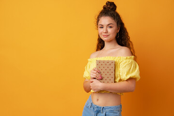 Young curly woman student holding book against yellow background