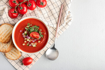 Bowl with tasty gazpacho and bread slices on light background
