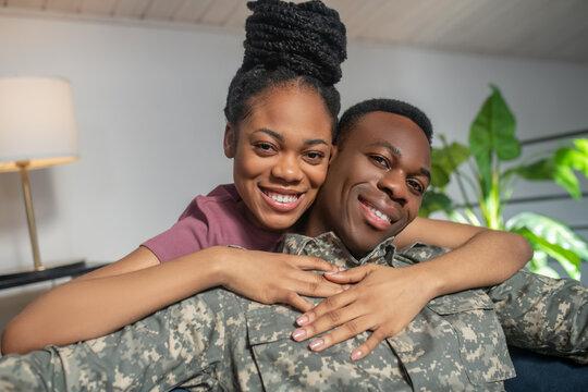 Shining woman hugging man in military uniform