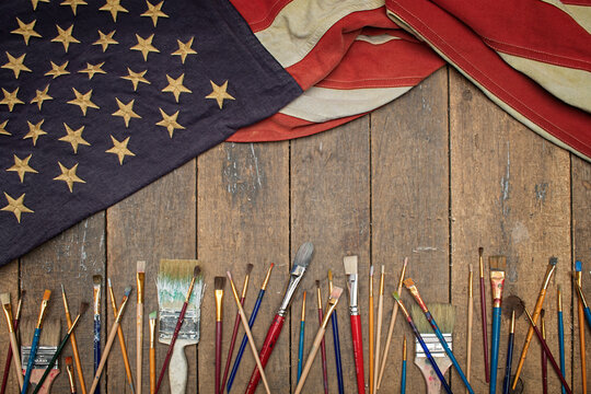 Antique American flag drapped on an old work bench with artists brushes
