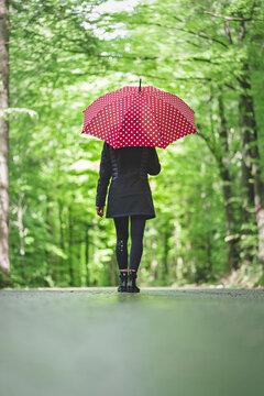 Frau mit rotem Regenschirm bei Spaziergang