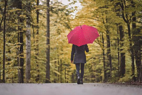 Frau mit rotem Regenschirm im Herbstwald