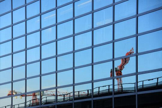 Baukräne spiegeln sich in Glasfassade
