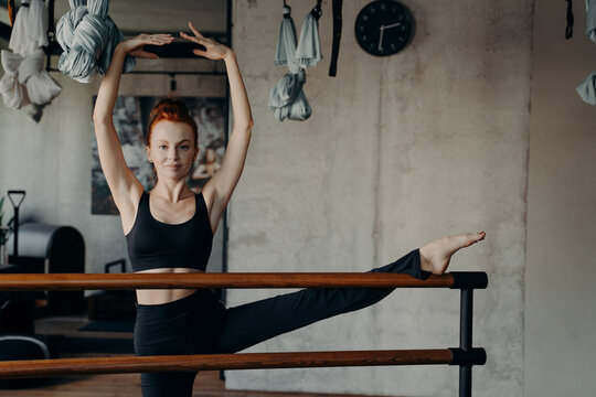 Beautiful slim redhaired woman standing with leg on ballet barre