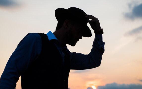 man dancer silhouette pose with hat against sunset sky, silhouette