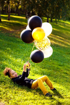 A little African girl is playing in an outdoor park. He is lying on the grass and holding multicolored gold, black, and silver balloons in his hands.