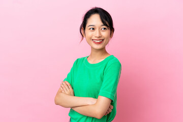 Fototapeta Young Vietnamese woman isolated on pink background with arms crossed and looking forward obraz