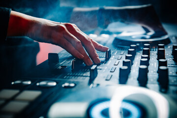Fototapeta DJ Hands creating and regulating music on dj console mixer in concert nightclub stage obraz