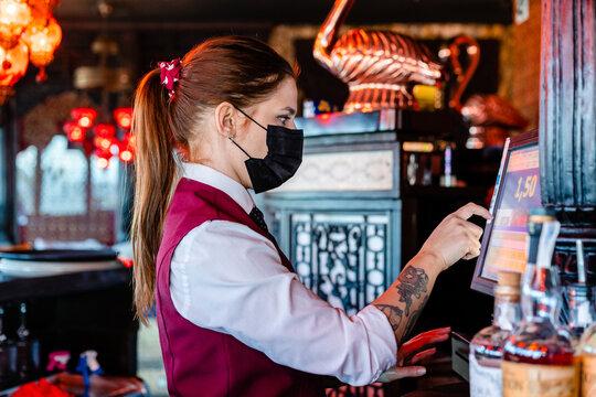 Bartender using cashier in bar