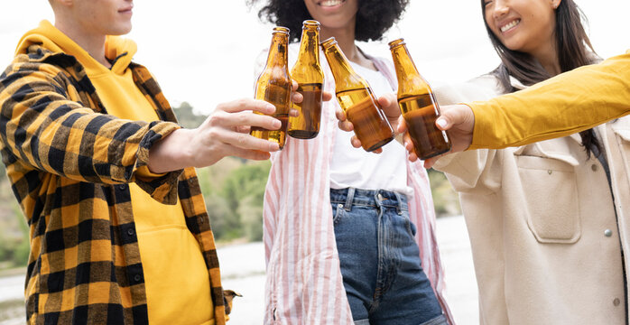Multiethnic friends clinking beer bottles near river