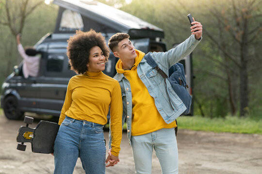 Multiethnic young couple taking selfie in countryside