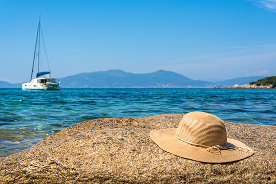 Straw hat on the top of the huge rock in a middle of Ajaccio gulf with the yacht and the Mediterranean sea on the background.