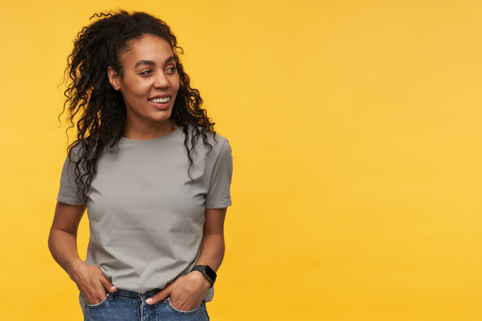 smiling african american young female keeps her hands in pocket, feel happy and satisfied looks aside at cop space isolated over yellow background