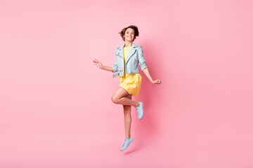 Photo of sporty lady jump beaming shiny smile wear yellow short dress footwear isolated pink color background Wall mural