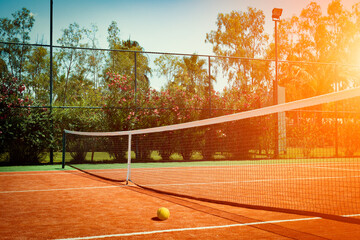 Obraz Wide angle photo of artificial grass tennis court with tennis ball during sunset. Competitive individual sports concept. - fototapety do salonu